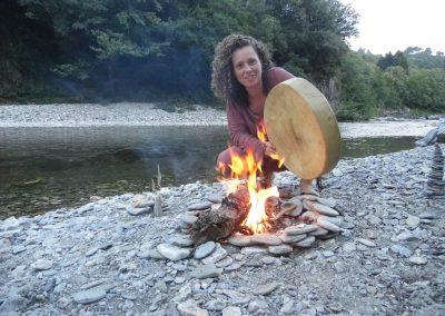 Marion et son tambour devant un feu au bord de la rivière